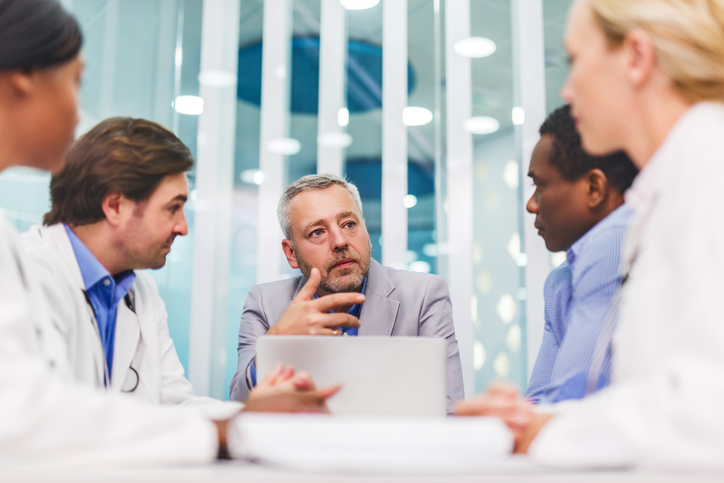 Businessman talking in a meeting with doctors.