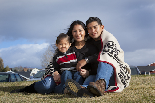 Native family sitting under a blanket