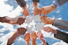Multi-ethnic hands jointly holding 4 puzzle pieces