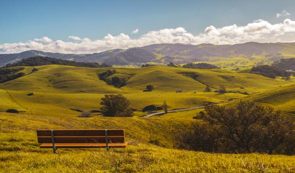 A bench seated on a plain overlooking more hills and plains