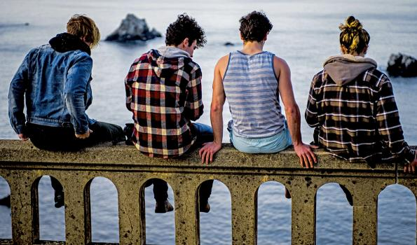 Photo of Four Young Adults, Sitting on a Pier -Photo by Sammie Vasquez