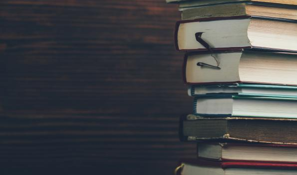 stack of textbook on a dark background