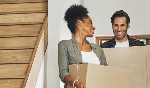 Couple smiling while carrying moving boxes